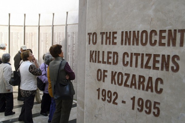 People stand in front of a monument with the names of 1,226 victims killed in the summer of 1992 at the beginning of the Bosnian war, during a ceremony to mark the 19th anniversary of the war, in the village of Kozarac